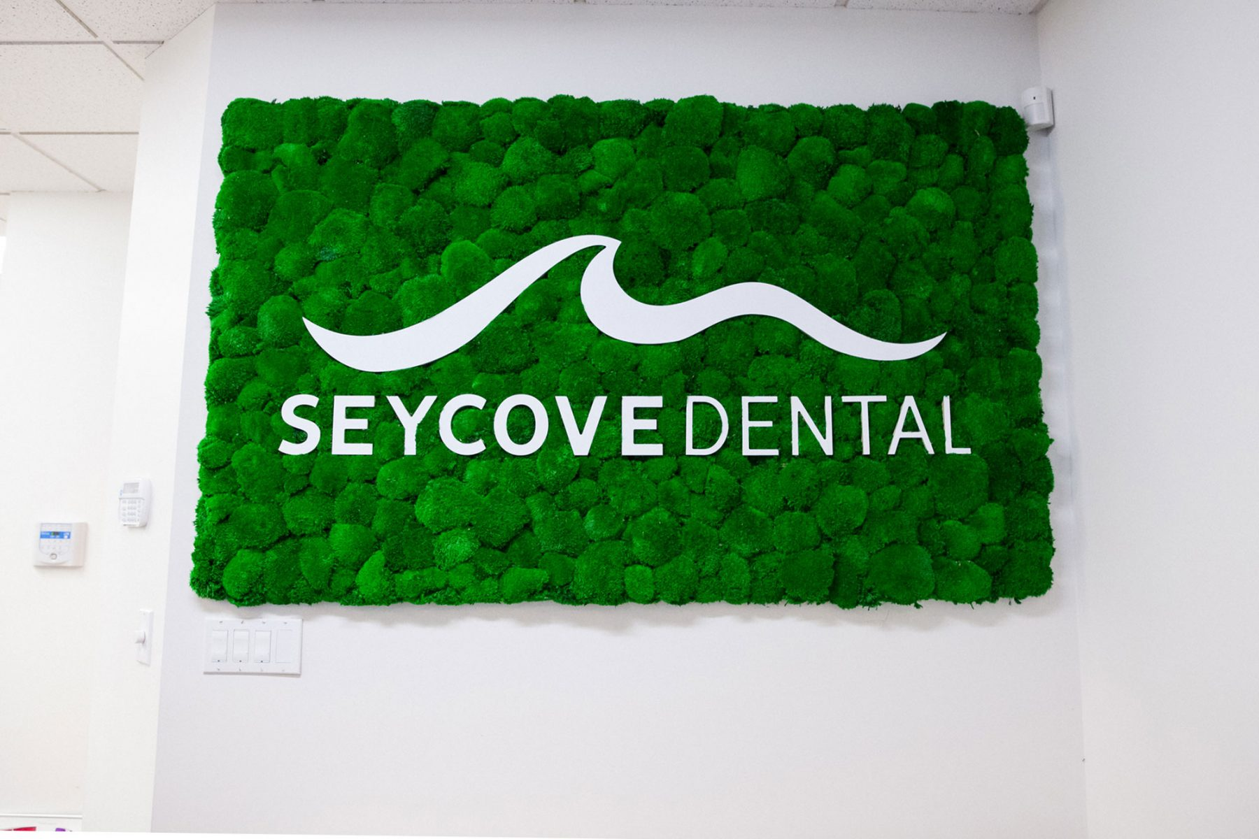 front lobby sign that reads Seycove Dental in white on a green background