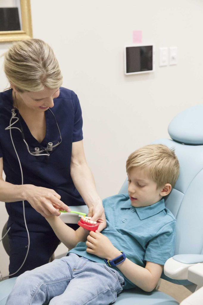a dentist shows a child how to brush using a teeth model while the child sits in the dental chair