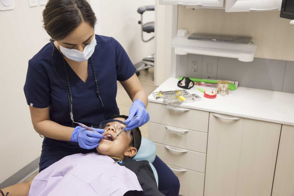 a dentist inspects a young patient's teeth with dental tools